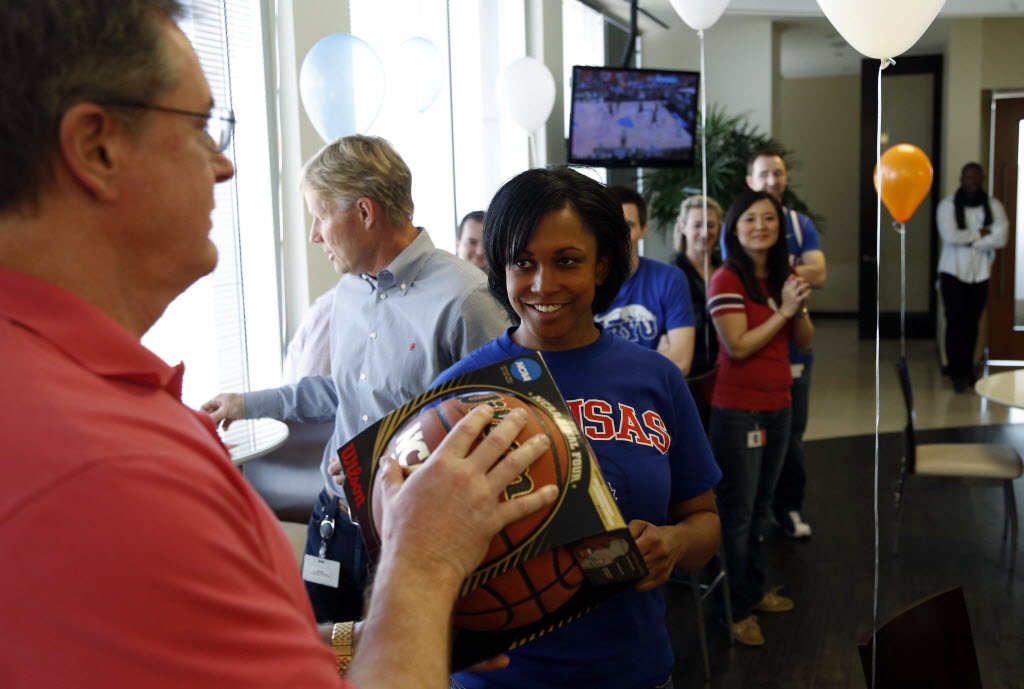 Ed Heffernan, president and CEO (left), gives a basketball to Brionna Jackson after she won the raffle during a NCAA Tournament party at Alliance Data Systems in Plano last year. (Vernon Bryant/The Dallas Morning News)