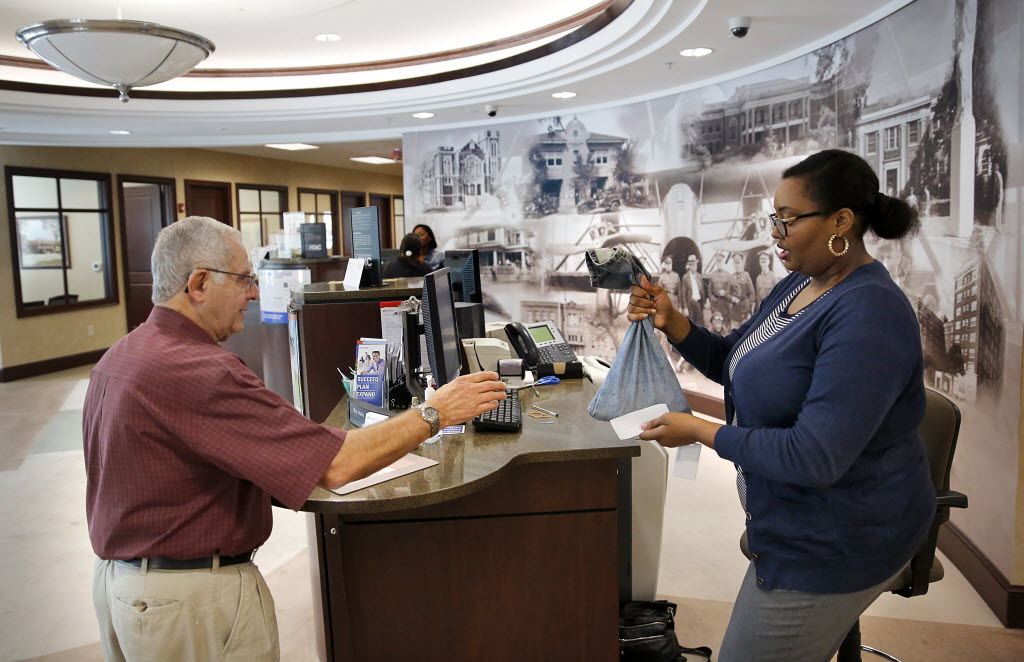American National Bank of Texas financial associate Misty Wells hands customer Frank Ashmore his change in a blue jeans money bag at the Oak Lawn location in Dallas in 2014. (Tom Fox/The Dallas Morning News)