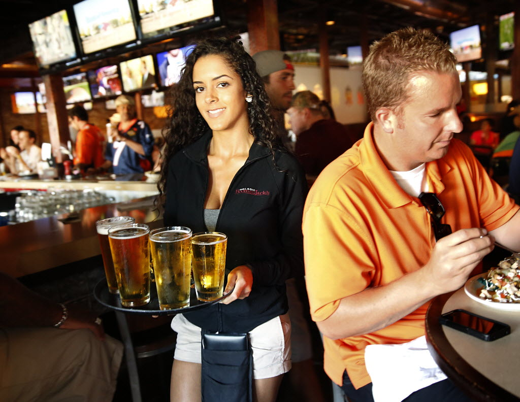 BoomerJack's Grill and Bar server Ajia Simmons delivered a tray full of cold beers at its North Arlington restaurant last year. (Tom Fox/The Dallas Morning News)