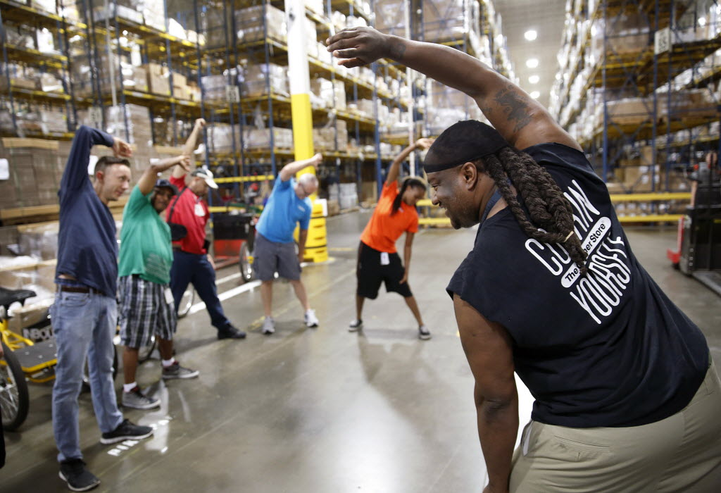 Container Store employee Sal Bowen (right) and his teammates stretched before their evening shift in the distribution center warehouse in 2014. (Tom Fox/The Dallas Morning News)
