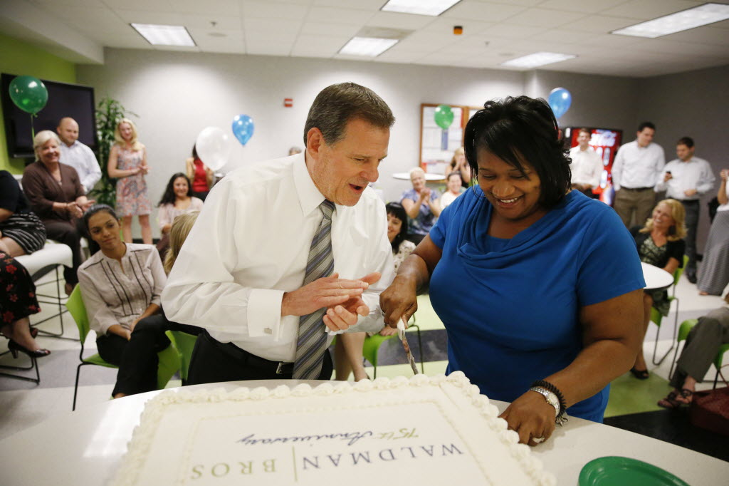 Stephen Waldman (left) helps Debra Henderson cut an anniversary cake during a new business raffle at Waldman Bros. offices in Dallas in 2014. (Andy Jacobsohn/The Dallas Morning News)