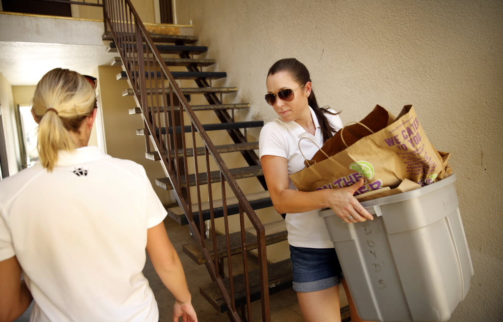 Frontline Source Group employees Lea Zortman (right) and Katharine Rosebrock deliver back-to-school supplies at Brentwood Apartment Homes in East Fort Worth as they volunteer with Mission Arlington. (Tom Fox/The Dallas Morning News)