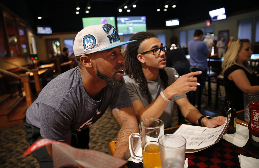Evantage employees Anthony Hubbard (left) and Josh Ard confer before making a pick during a company Fantasy Football Draft at the Fox and Hound Sports Tavern in Dallas on Aug. 26. (Tom Fox/The Dallas Morning News)