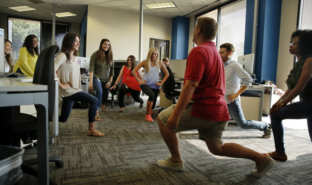 Viverae marketing employees (from left) Amanda Lam, Taunya Williams, Taryn Haney, Meredith Otte, Allison Lee, Molly Cannon, Jed Rullman (foreground) Andy Jones and Sal Gregory do lunges at work. (Tom Fox/The Dallas Morning News)
