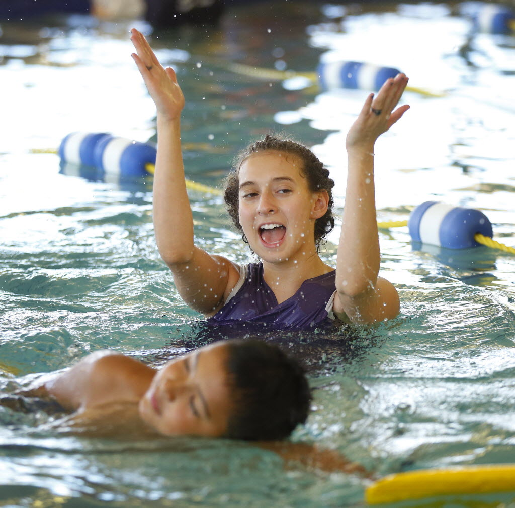 Emler Swim School instructor Megan Madigan applauds 8-year-old Eric Hernandez on his form during a lesson at its Allen location. (Tom Fox/The Dallas Morning News)