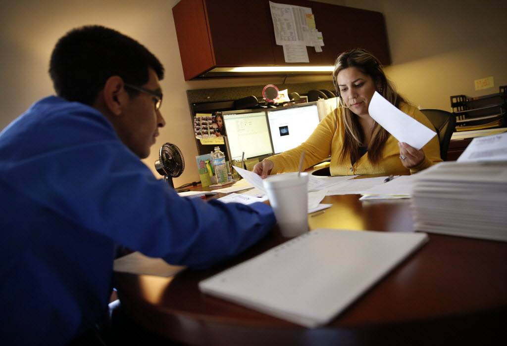 Jim Adler and Associates' Cristal Sanchez (right) works with case manager in training Roy Ferretiz. (Tom Fox/The Dallas Morning News)