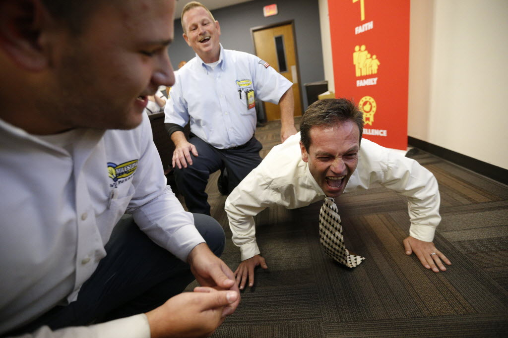 At an employee meeting, Joel Hamnes, install manager (right), competes in a push-up competition to win tickets to Van Halen with encouragement from Bobby LeFlore (center) and Daniel Ruiz. (Nathan Hunsinger/The Dallas Morning News)