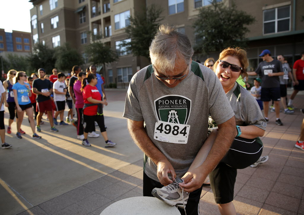 Pat Rincon (right) of Pioneer Natural Resources has her shoe tied by her husband Matt Rincon as they get ready for the Richardson Corporate Challenge 5K Run in September at Galatyn Park in Richardson. (Tom Fox/The Dallas Morning News)