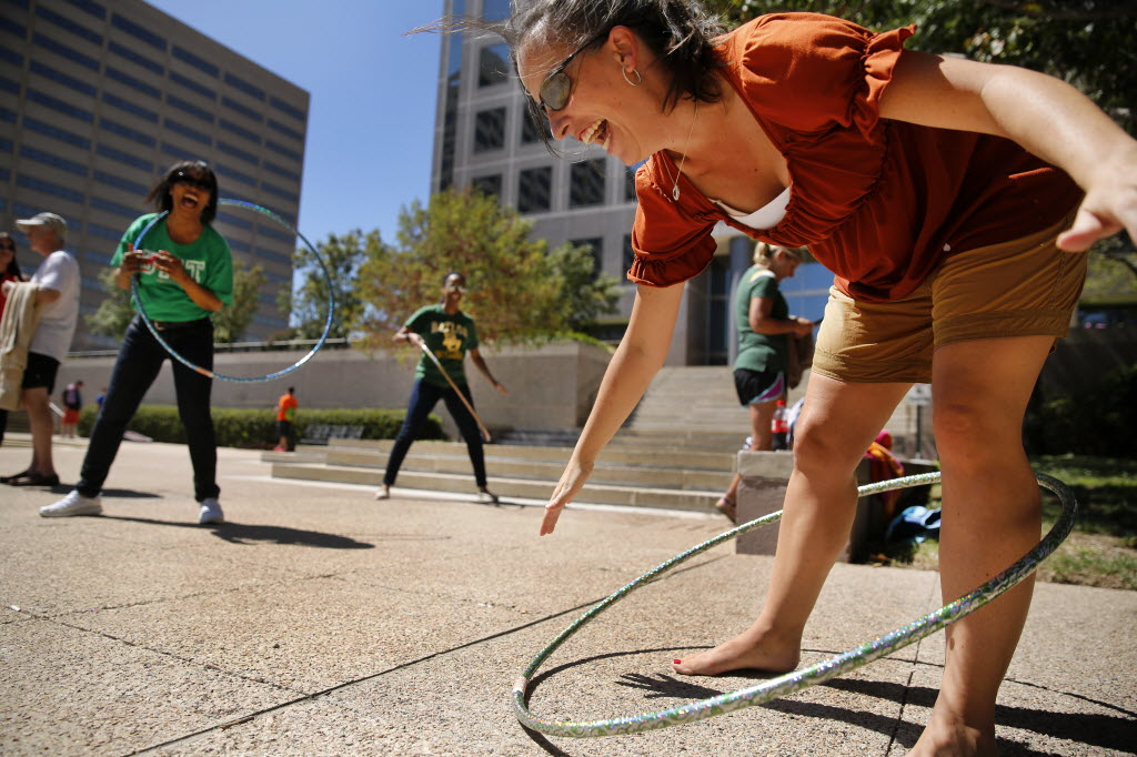 Encompass Home Health and Hospice vice president of finance Jennifer Polak (right) and accounting manager Cheryl Aldridge (left) hula hoop during their company tailgate party in September. (Tom Fox/The Dallas Morning News)