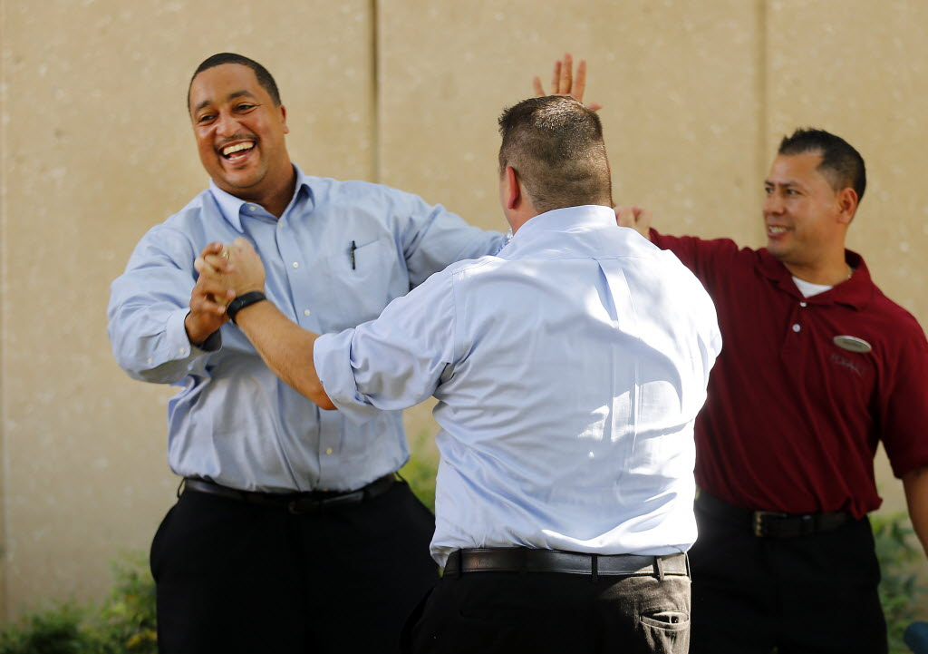 Hyatt Regency DFW security supervisor Antwan Simpson (left) is congratulated by Jonathan Chaplowe (center) after he won a paid day off. The hotel's management was celebrating International Housekeepers Week. (Tom Fox/The Dallas Morning News)