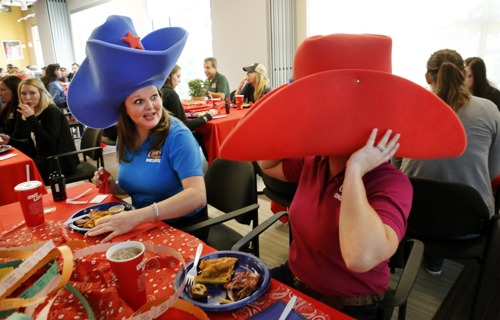 Raising Cane's Chicken Fingers senior office services manager Kellye Ready (left) is surprised when payroll specialist Courtnay Wallen's oversized foam cowboy hat falls down over her head during a quarterly employee appreciation event at the company's Plano office. (Tom Fox/The Dallas Morning News)