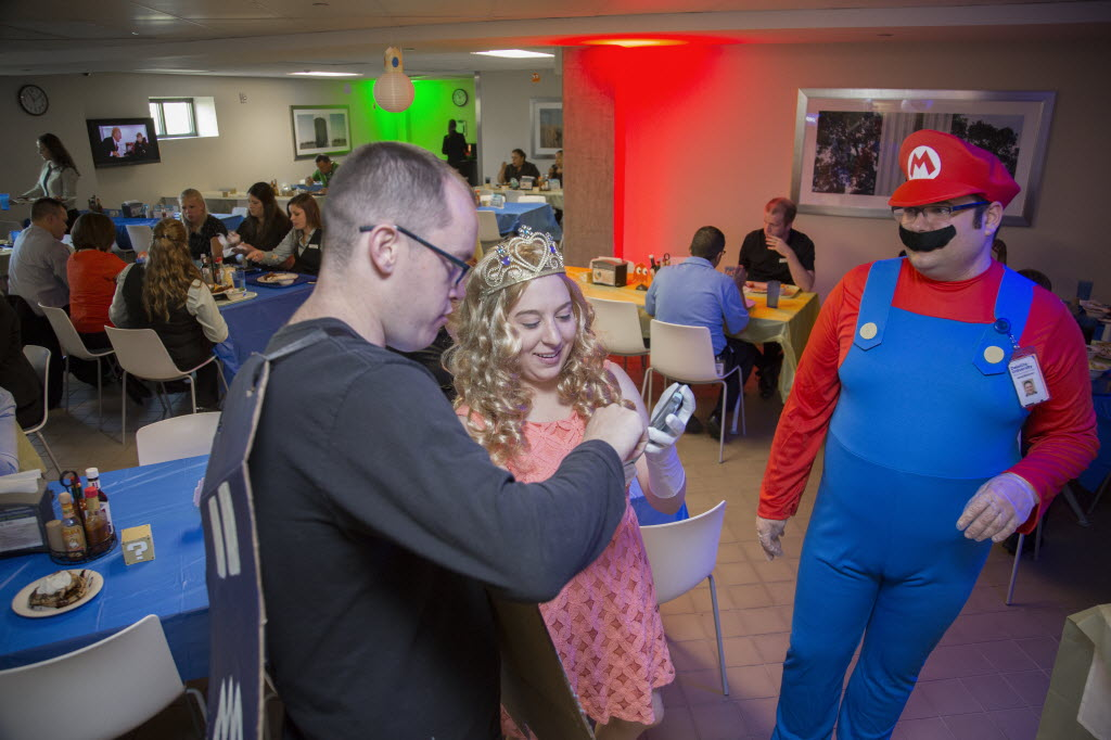 Benchmark Hospitality of Texas employee Dustin Foster showed a picture to Charity Wooley during a cafeteria takeover event at Deloitte University in Westlake in 2015. At right is Jerod Blackman in the Mario costume. (Kye Lee/Special Contributor)