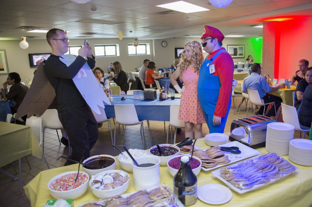 "Benchmark Hospitality of Texas held a ""retro arcade"" in September. From left: Dustin Foster photographs Charity Wooley in a princess costume and Jerod Blackman in a Mario costume. (Kye Lee/Special Contributor)"