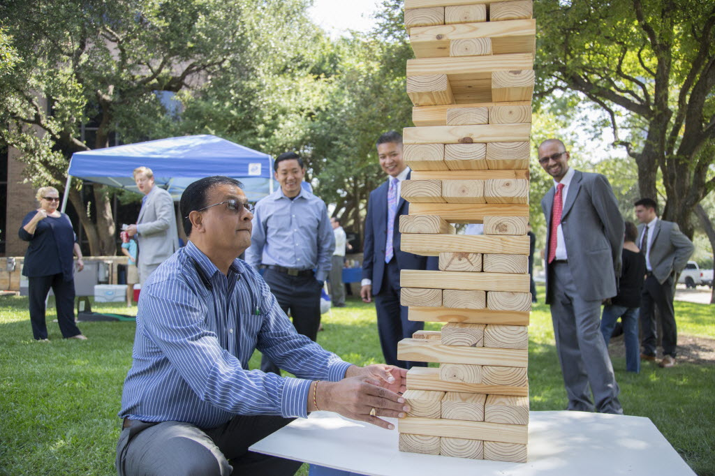 Hemant Patel, a New York Life agent, plays a life-size Jenga game during a party to kick off the fourth quarter. (Kye Lee/Special Contributor)