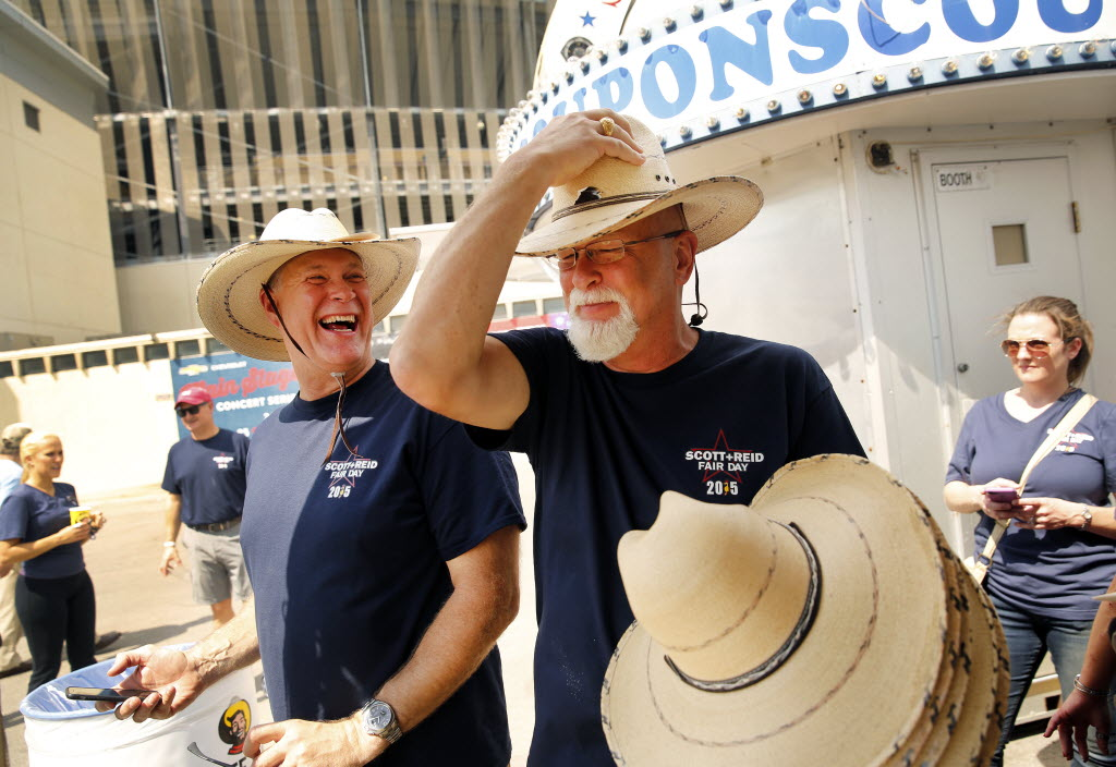 Scott + Reid General Contractors vice president and partner Jeff Reid (right) tries on straw hats with his brother, company president Brad Reid, at the State Fair of Texas. (Tom Fox/The Dallas Morning News)