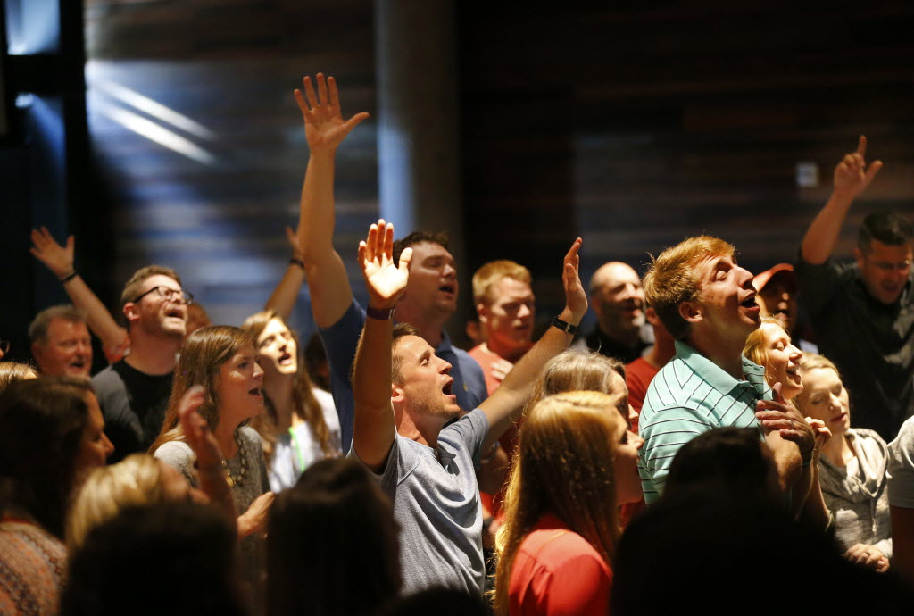Watermark Community Church employees join together for a Tuesday staff prayer. (Tom Fox/The Dallas Morning News)