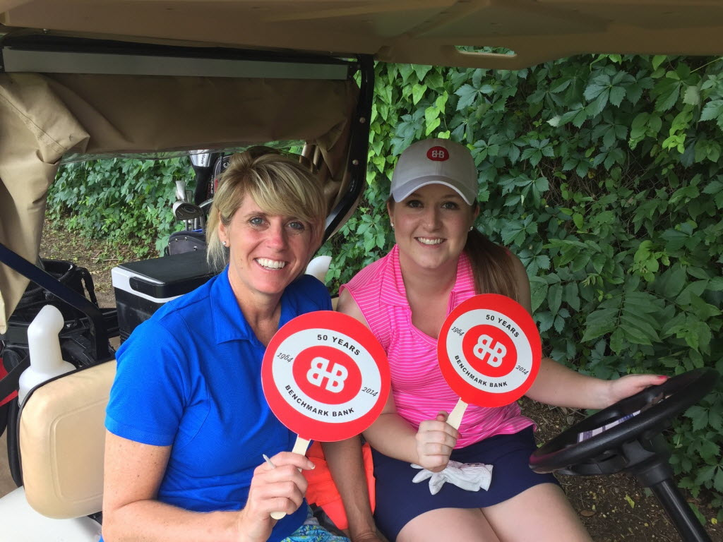 Benchmark Bank & Title employees Laurie Pool (left) and Courtney Brewer represented the company at a charity golf tournament. (Benchmark Bank & Title)