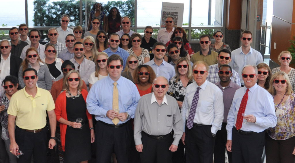 JLL employees celebrated the highlights from 2014 at a party with cake and champagne in the lobby of the JLL Dallas corporate office. And everyone wore shades, including Roger Staubach (front row, third from right). Staubach founded the Staubach Co., which merged with JLL in 2008. (JLL)