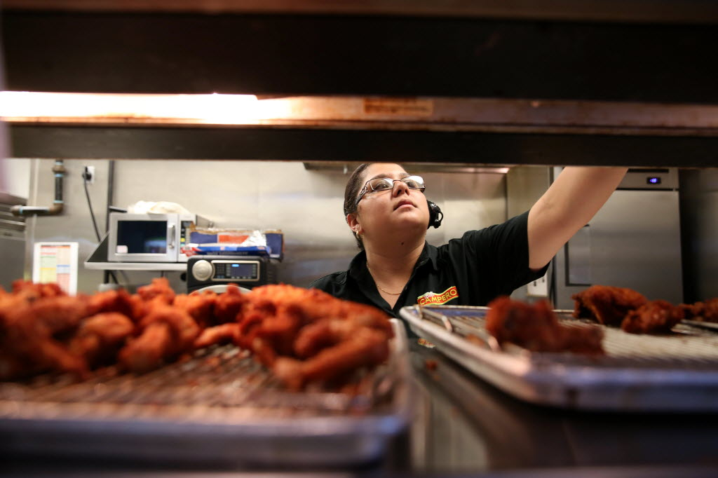 The leisure and hospitality industry continues to post sizeable job gains in Texas — up 5,200 in June and nearly 54,000 from a year ago. Here, supervisor Dinora Leiva preps an order at Pollo Campero, a Latin American chicken chain that's expanding in the Dallas-Fort Worth market.