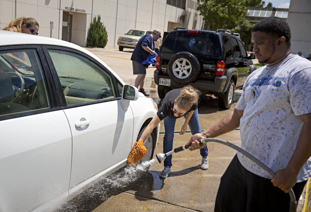 Marcus Washington (right), an income auditor at Omni Dallas Park West Hotel, and Shayla Truesdell wash a colleague's car in August in Dallas. Employees at the hotel spent part of the afternoon washing cars to raise money for the American Heart Association. (G.J. McCarthy/The Dallas Morning News)