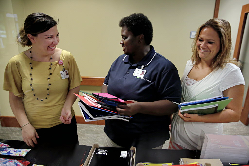 From left: April Garcia, a human resources manager with Erickson Living, smiles as she helps Highland Springs employees Ronder Day and Brittany Jordan pick out school supplies in Plano. Each year, Highland Springs offers free school supplies to employees with children or grandchildren in need. (G.J. McCarthy/The Dallas Morning News)