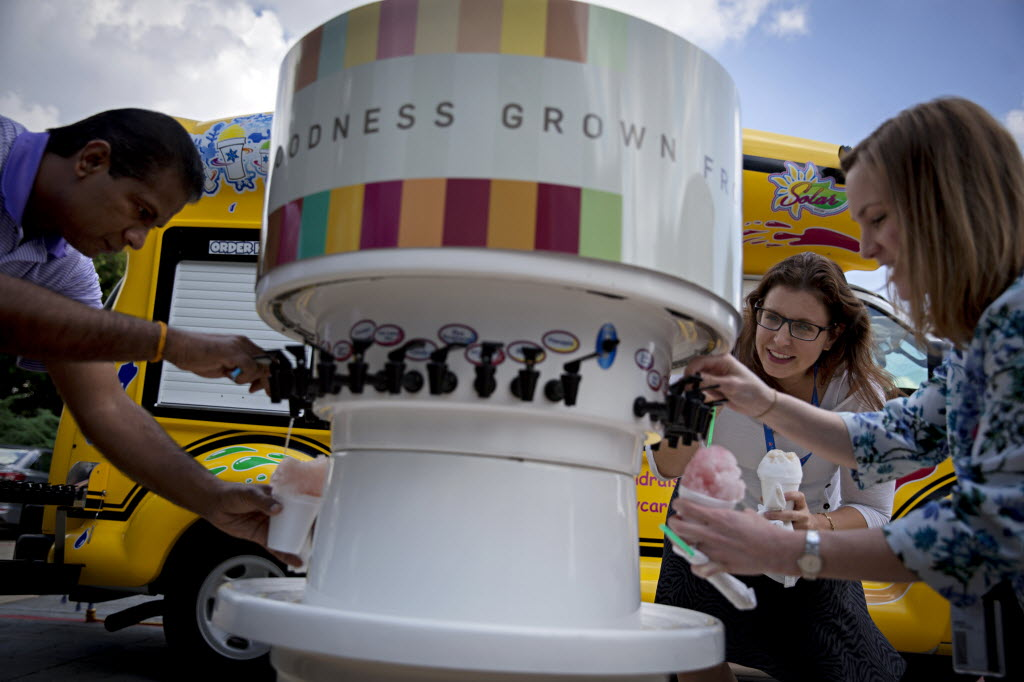 From left: Tamilmani Kamalanatha, Elena Mappus and Laura Lyon mix flavors on their snow cones outside Intel Security's corporate headquarters in August in Plano. The company provided the treats for employees to enjoy on their lunch break. (G.J. McCarthy/The Dallas Morning News)