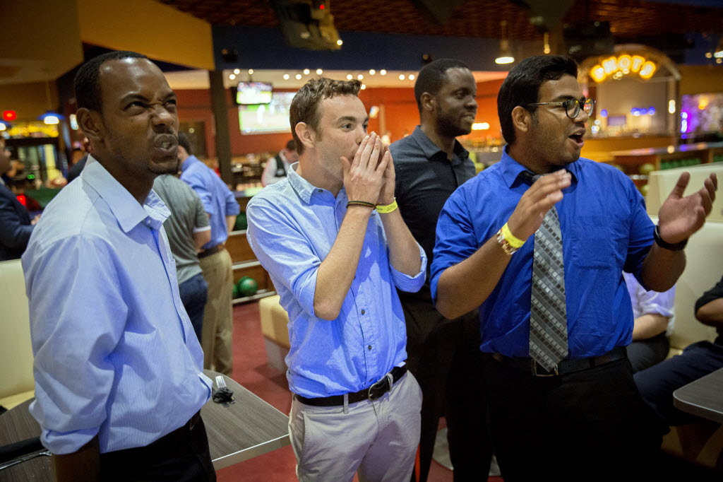 From left: Darrion Reynolds, Connor McNeil and Sagar Nandal cheer as a colleague gets a the spare while bowling at Main Event in Frisco. Evantage plans outings on Monday nights outside of the office to build camaraderie and blow off steam. (G.J. McCarthy/The Dallas Morning News)