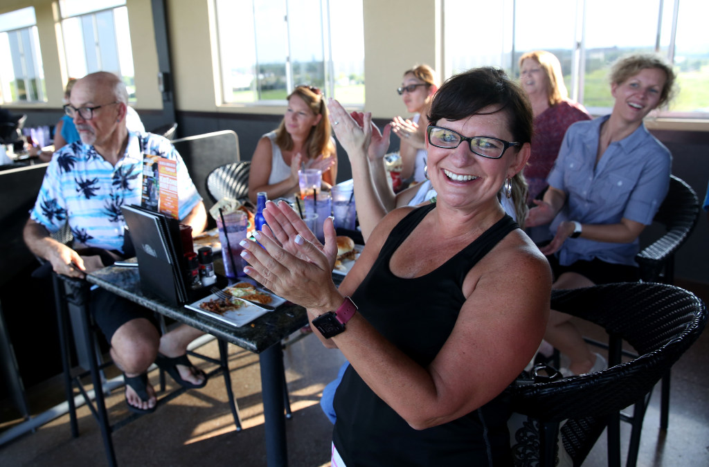 Angie Edie, an HR representative at Jack Henry & Associates Inc., and her coworkers cheer during the company's annual team building event at Topgolf in Allen. (Rose Baca/The Dallas Morning News)