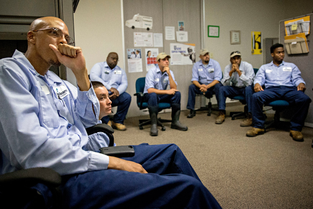 Tre McFadden (left) and fellow employees take part in a morning team meeting at HomeTeam Pest Defense's West Dallas branch in Grand Prairie. (G.J. McCarthy/The Dallas Morning News)