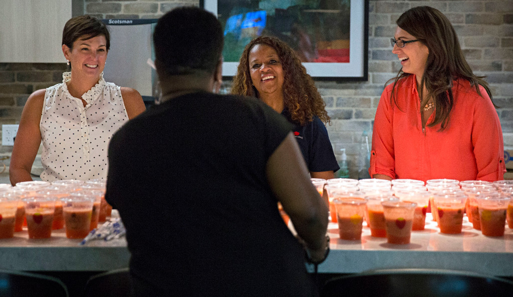 From left, facing camera: Susan Bryan, Gloria Brown and Meagan Reynolds laugh as they serve smoothies during an Employee Engagement Committee event at PrimeLending in September. (G.J. McCarthy/The Dallas Morning News)