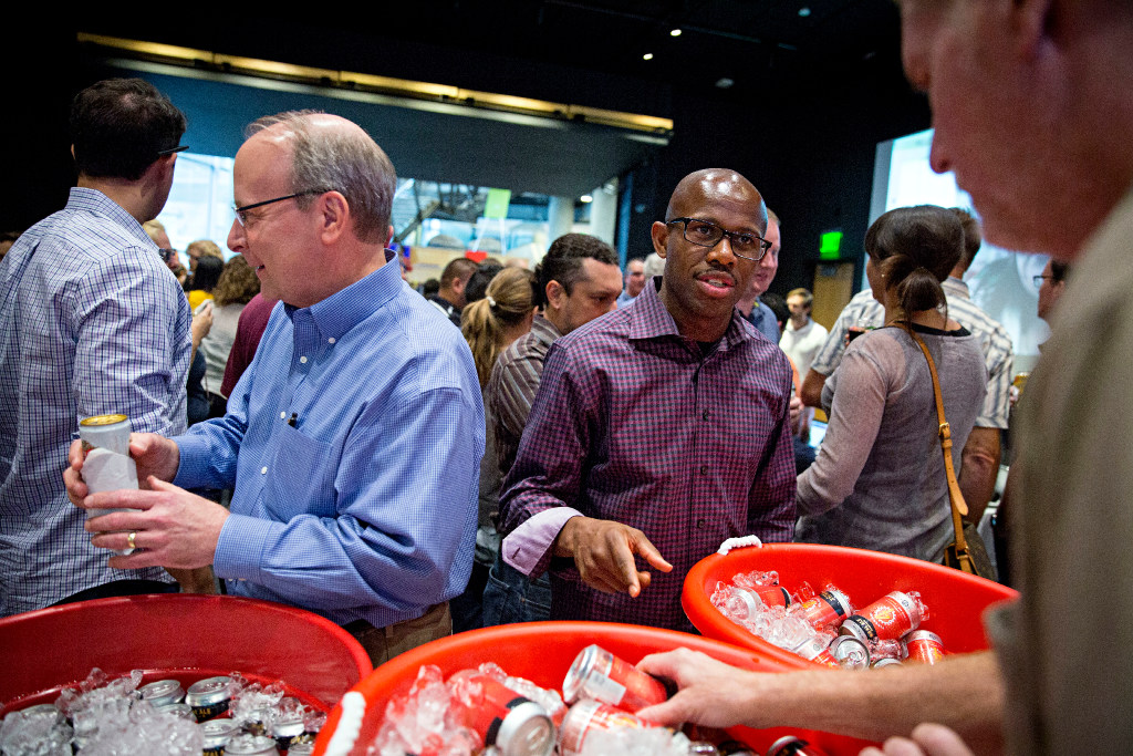 Kirk Krueger (left) walks away with his beer as colleague Jimah Rogers goes over his choices during a happy hour event for employees at HKS Architects in September in Dallas. (G.J. McCarthy/The Dallas Morning News)