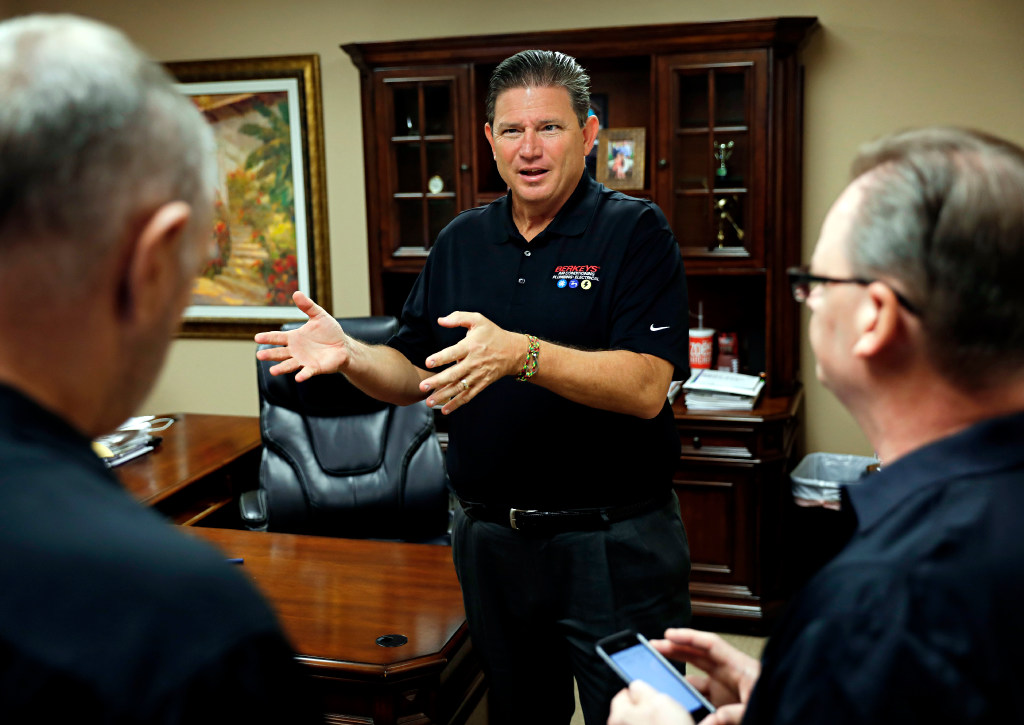 Jamie Wooldridge (center), president of Berkeys Air Conditioning, Plumbing & Electrical, talks with equipment specialist Mike Tanna (left) and operations manager Lee Pogue at the company's offices in Southlake. (G.J. McCarthy/The Dallas Morning News)