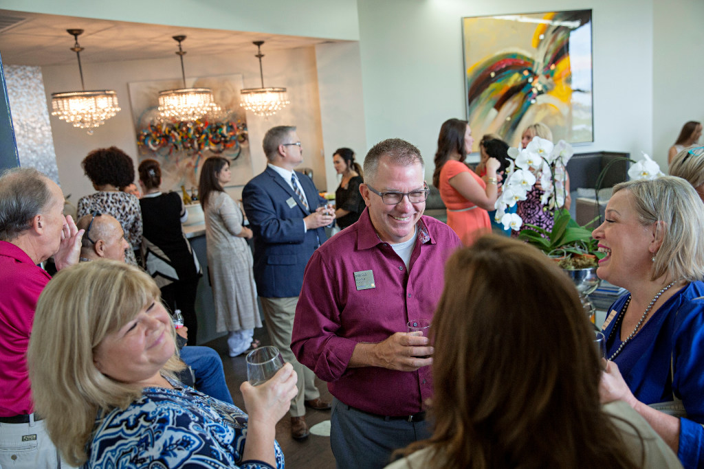 Lynn Carlton, Patrick Burke and Valerie Keener laugh as they visit before the unveiling of a new Art of Nathan Grace collection in Frisco. (G.J. McCarthy/The Dallas Morning News)