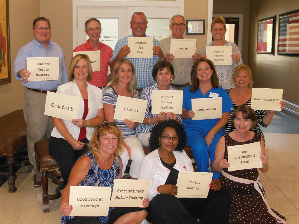 Ardent Hospice employees posed for a team photo holding cards representing the things they do well. (Tiffany Ihnfeldt)