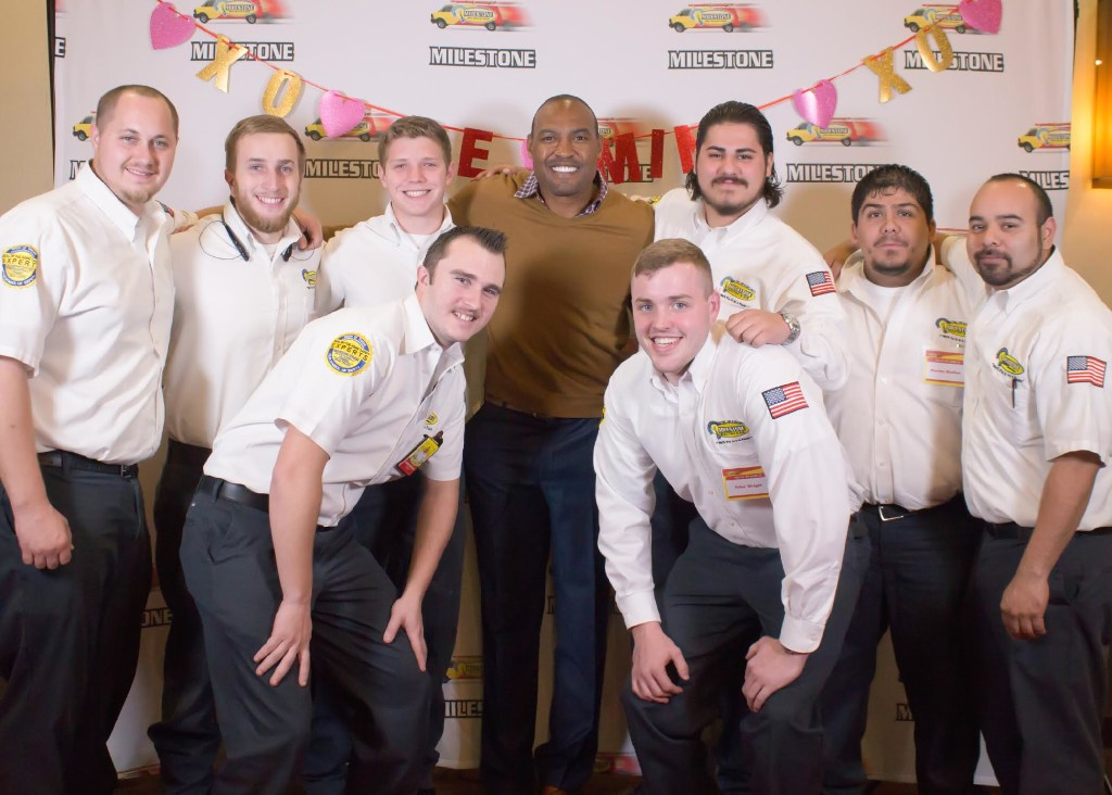 Milestone Electric technicians pose with former Dallas Cowboys player Darren Woodson, who was a guest speaker at the company's monthly family meeting. (Milestone Electric)