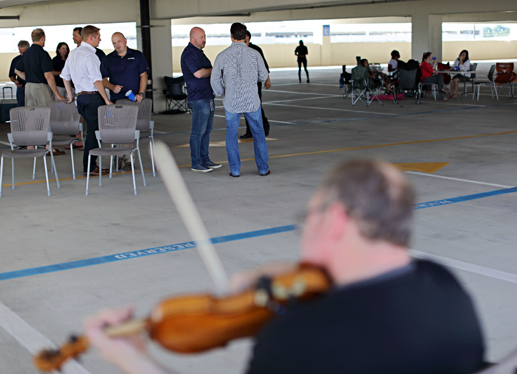 Employees at Kosmos Energy enjoy live music during a happy hour event in Dallas. (G.J. McCarthy/The Dallas Morning News)