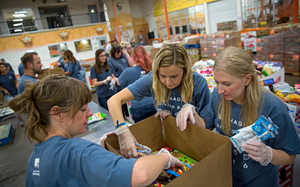 From left: TPN employees Amanda Pounds, Holly Durnin and Helen Kahl pack a box as they volunteer at the North Texas Food Bank in Dallas. (G.J. McCarthy/The Dallas Morning News)
