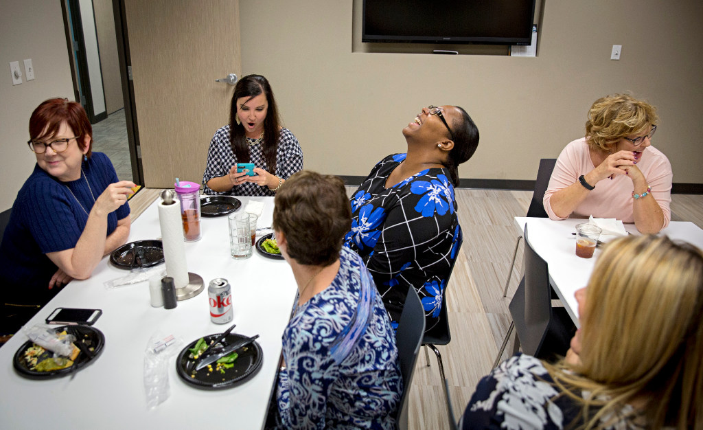 From left back row: Goranson Bain employees Shannon Armstrong, Brie Ramirez, Britney Harrison Dieng and Debby Reeves laugh during staff lunch. Once a month, employees at the family law practice are treated to a meal. (G.J. McCarthy/The Dallas Morning News)