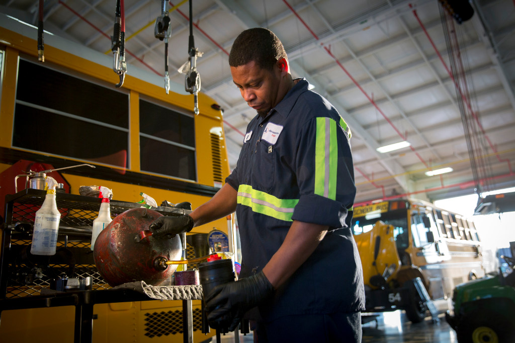 Sidney Bishop, a mechanic with the Allen Independent School District, performs preventive maintenance of school buses at the district's service center in Allen. (G.J. McCarthy/The Dallas Morning News)