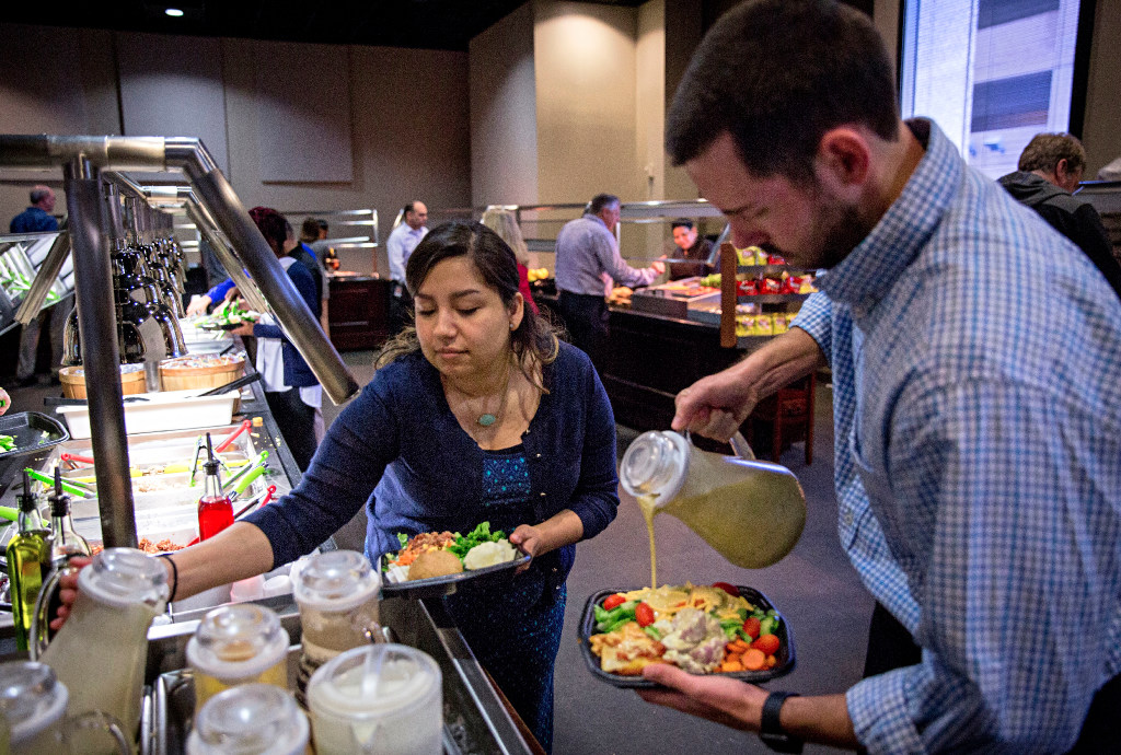 Melissa Harp (center) and Michael Wash serve themselves lunch at Pioneer Natural Resources' cafeteria at company headquarters. The buffet lunch is provided to employees free of charge. (G.J. McCarthy/The Dallas Morning News)