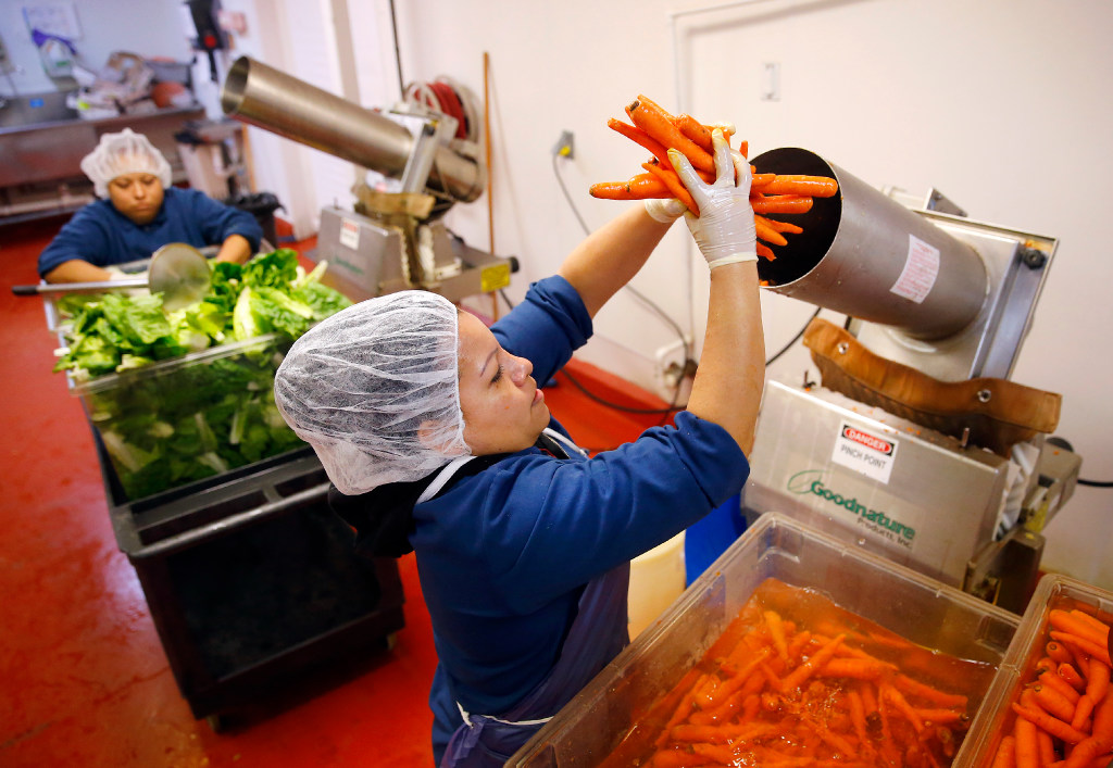 Marsala Giron loads a juicer with carrots to make Vim Vitae's natural, organic juices at their Dallas facility, Wednesday, January 18, 2017. Their CEO Nick Mysore, who is a veteran of Dean Foods and ConAgra, was hired to turn Vim Vitae, a Dallas-based healthy juice company, into a national brand after a private equity investment.