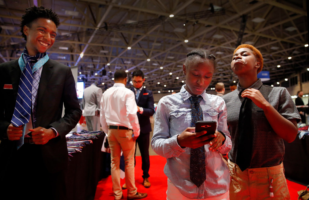 Tykia Evans of Dallas (right) takes pride in his tie he learned how to put on by Foley's human resources employee Tim Baker (left) during the Opportunity Fair and Forum at the Kay Bailey Hutchison Convention Center in Dallas, Friday, May 19, 2017. Joining Tykia in receiving a lesson and free tie is his friend, Jermelin Souter of Dallas (center) as the young men looked for jobs.