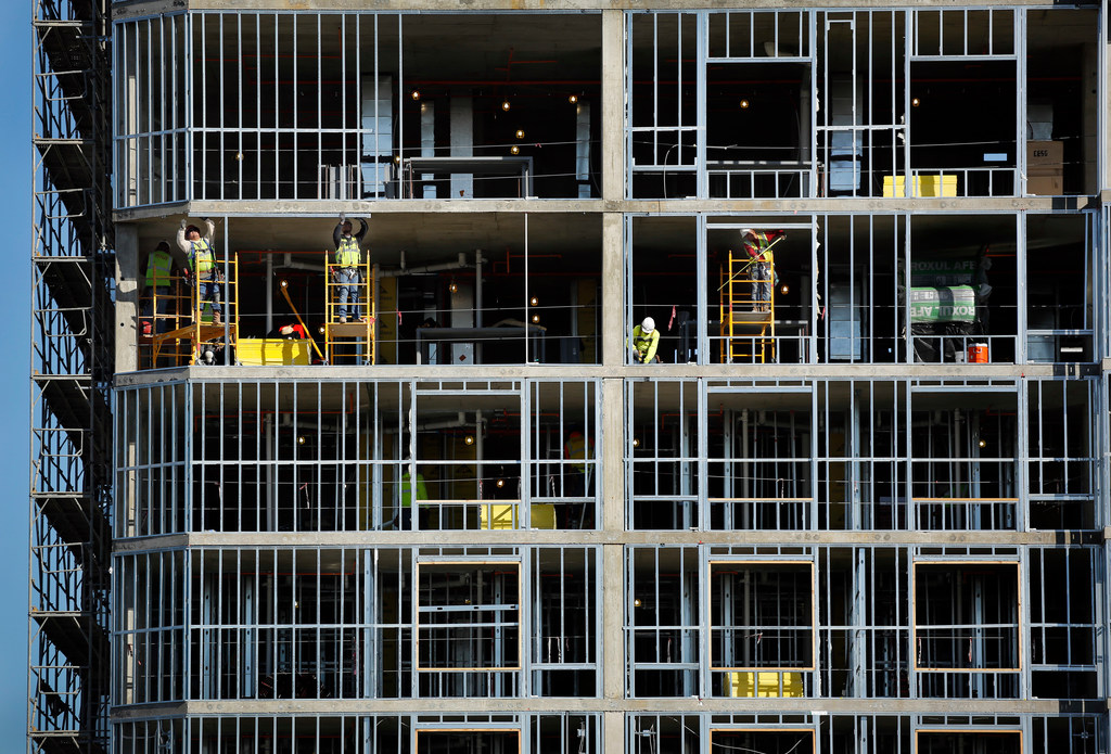 Construction workers are seen building the new, 12-story Courtyard by Marriott hotel near Union Station in downtown Dallas. The leisure and hospitality sector led Texas' job growth in October with 34,700 new jobs.