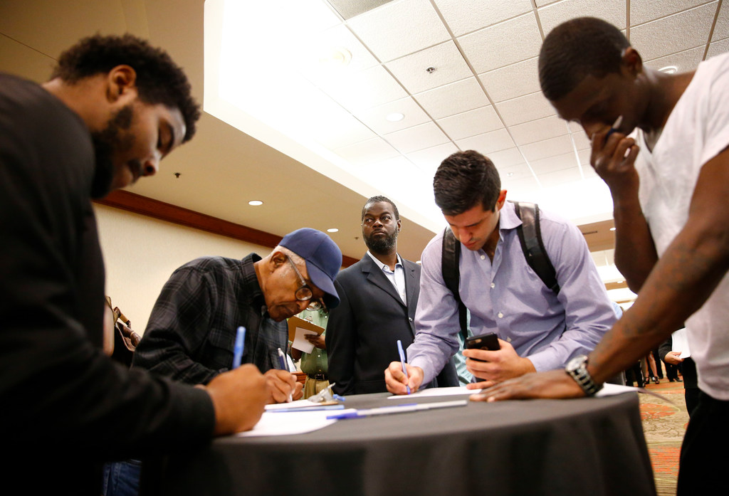 "People fill out forms during the ""You're Hired Job Fest"" at the Sheraton Dallas Hotel in Dallas on Oct. 26, 2017."